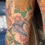 Healed tattoo on a woman's heavily tattooed legs. Yellow Chrysanthemum and Butterfly with a Woman's head, a Yokai and Cherry Blossoms by Tattoo Artist, Harriet Street at Cult Classic Tattoo, Romford, Essex, London