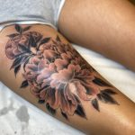 A woman with a large black and grey, fine line tattoo of a Peony flower on her thigh by Harriet Street Tattoo