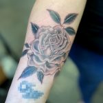 Fine line black and grey rose on a woman's forearm, tattooed by Harriet Street at Cult Classic Tattoo in Romford