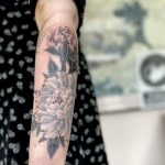A woman's forearm, with a fine line black and grey Japanese style tattoo of a peony. Floral tattoo by tattoo artist Harriet Street