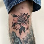 Realistic black and grey lily tattooed in a fine line style. Floral tattoo by Harriet Street