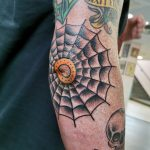 A man's elbow, tattooed with a black spiderweb in a western traditional style by northernbuilt, Ant Dickinson