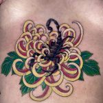 A speckled black scorpion, sitting inside a yellow and pink chrysanthemum in a japanese style. It is tattooed on a woman's sternum by Harriet Street at Cult Classic Tattoo in Romford, Essex