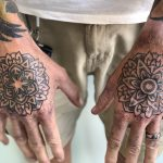 A man's hands, both tattooed with mandalas, with dot work shading by Mike Wall of Cult Classic Tattoo