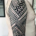 A man's arm, tattooed with a half sleeve of polynesian inspired tribal by Mike Wall